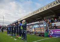 Wycombe coaching staff & substitutes join in a minutes applause in memory of the late Graham Taylor during the Sky Bet League 2 match between Wycombe Wanderers and Yeovil Town at Adams Park, High Wycombe, England on 14 January 2017. Photo by Andy Rowland / PRiME Media Images.