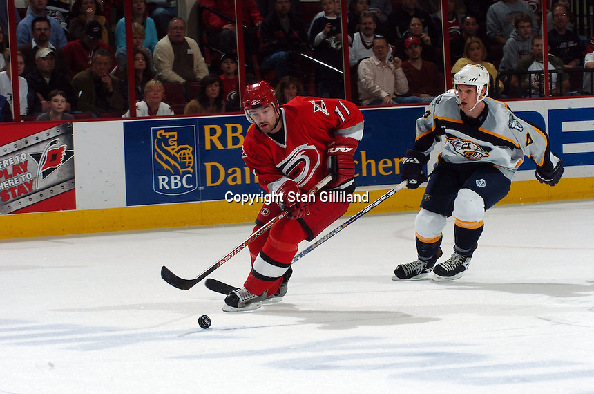 The Carolina Hurricanes' Justin Williams (11) controls the puck defended by the Nashville Predators' Mark Eaton (4) during their game Friday, January 13, 2006 in Raleigh, NC. Carolina won 5-4 after a shootout.