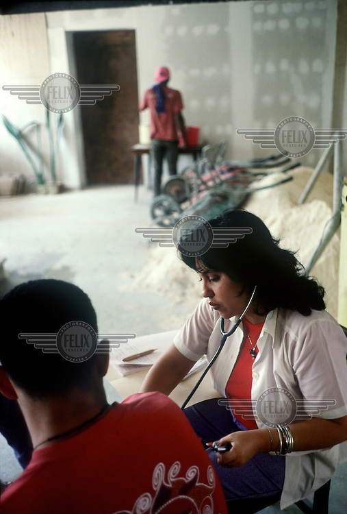 A doctor examines a construction worker during a workplace health check at a building site in Havana.