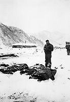 A wounded chaplain reads a memorial service over the snow-covered bodies of dead Marines.  Koto-ri, Korea.  December 3, 1950.  Cpl. W. T. Wolfe.  (Marine Corps)<br /> NARA FILE #:  127-N-A5552<br /> WAR & CONFLICT BOOK #:  1512