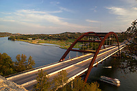Boaters pass underneath the 360 Bridge (Pennybacker Bridge) surrounding hills and lake austin, Texas, USA