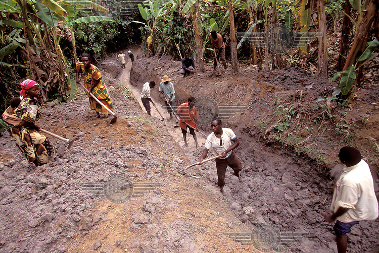 © Caroline Penn / Panos Pictures..Mpigi, near Bule, UGANDA. 07/1999..The villagers of Luwinga work together clearing mud from the spring which is their main water supply.