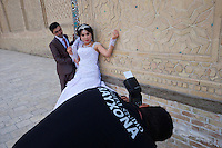 Uzbekistan, Bukhara. Kalon Ensemble. Wedding couple taking photos.
