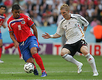 JUNE 9, 2006: Munich, Germany: Costa Rican forward (11) Ronald Gomez tries to move past German midfielder (7) Bastian Schweinsteiger during the World Cup Finals in Munich, Germany. Germany defeated Costa Rica, 4-2.