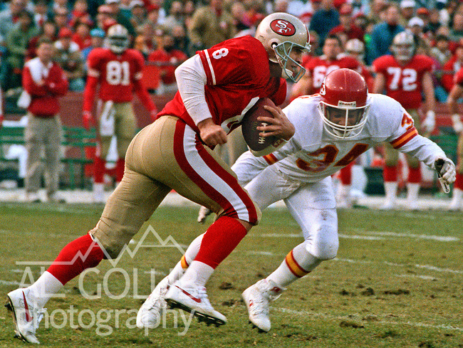 San Francisco 49ers vs. Kansas City Chiefs at Candlestick Park Saturday, December 14, 1991.  49ers beat Chiefs 28-14.  49ers quarter back Steve Young (8) attempts to out run Chiefs defensive back Lloyd Burruss (34).