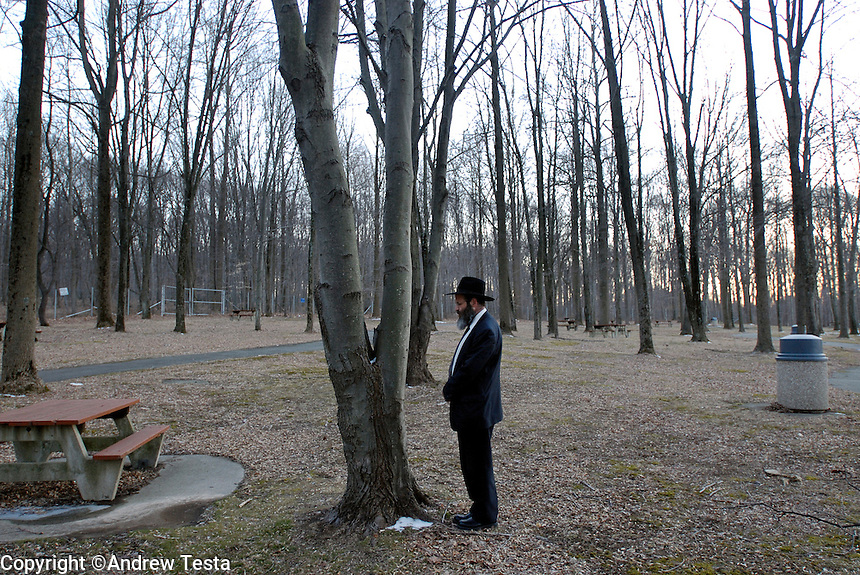 Rabbi Avrohom Stone prays at a rest stop in Pennsylvania on his way home, due to the pressures of his work, he often finds himself praying in unusual places..©Andrew Testa