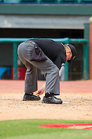 Home plate umpire Garrett Patterson cleans home plate during the Southern League game between the Montgomery Biscuits and the Chattanooga Lookouts at AT&T Field on July 23, 2014 in Chattanooga, Tennessee.  The Lookouts defeated the Biscuits 6-5. (Brian Westerholt/Four Seam Images)