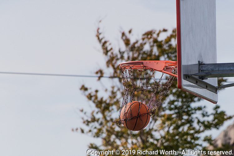A basketball passes through the hoop and chain-link net at an urban park on a spring afternoon.