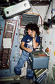 Astronaut Sally K. Ride, STS-7 mission specialist, communicates with ground controllers from the mid deck of the Earth-orbiting Space Shuttle Challenger during the STS-7 mission, June 18-24, 1983. She has just opened one of the large lockers during the operation and monitoring of the continuous flow electrophoresis system (CFES) experiment at left edge. This photograph was made with a 35mm camera.  Dr. Ride passed away due to Pancreatic Cancer on Monday, July 23, 2012..Credit: NASA via CNP