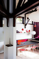 View into the 1960's style dining area with red pendant lights, a colourful banquette and Bertoia Diamond dining chairs surrounding the dining table