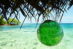 A green glass float hangs from a thatched roof, Bocas del Toro, Panama.