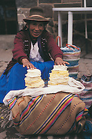 A cheese seller in Pisac Market points proudly to the produce that she has made on her smallholding. Pisac is in Peru's Sacred Valley of the Incas.