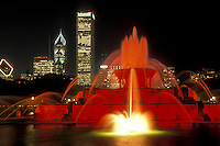 Chicago, Illinois, The Buckingham Memorial Fountain at Grant Park is illuminated at night by red lights. The illuminated skyline of downtown Chicago towers in the background.