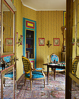 The walls of the games room are decorated with a striped yellow wallpaper which contrasts with the vibrant blue upholstered Louis XVI bergere chairs