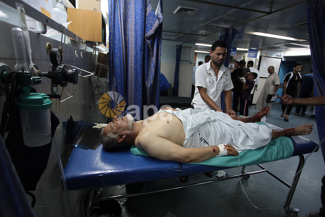 A Palestinian man, who medics said was injured by Israeli shelling, receives treatment at al-Shifa hospital in Gaza City on July 21, 2014. World efforts to broker a ceasefire in war-torn Gaza gathered pace as Israel pressed a blistering 14-day assault on the enclave, pushing the Palestinian death toll to 561. Photo by Ashraf Amra
