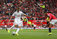 Pictured L-R: Gylfi Sigurdsson of Swansea against Tyler Blackett of Manchester, provides the cross to Ki Sung Yueng (not pictured) which he scored as his opening goal. Saturday 16 August 2014<br />