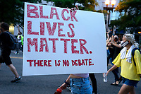 A demonstrator carries a sign during a protest in Washington, D.C., U.S., on Monday, June 1, 2020, following the death of an unarmed black man at the hands of Minnesota police on May 25, 2020.  More than 200 active duty military police were deployed to Washington D.C. following three days of protests.  Credit: Stefani Reynolds / CNP/AdMedia