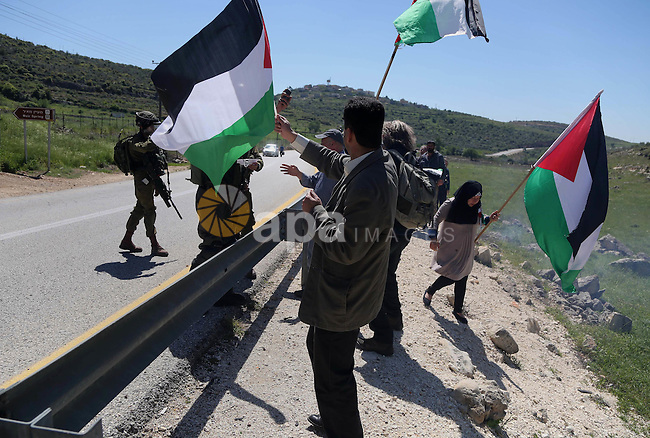 Palestinian protesters wave national flags in front of Israeli security forces during clashes following a march against Palestinian land confiscation on April 1, 2016 in the West Bank village of Nabi Saleh near Ramallah. Photo by Hamza Shalash