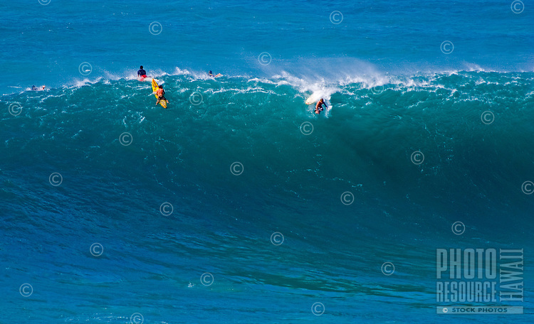 Surfer falling from the lip of a huge winter wave at Waimea Bay, on the North Shore of Oahu