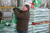 A farmer loading ewe nuts into a snacker <br /> &copy;Tim Scrivener Photographer 07850 303986<br /> ....Covering Agriculture In The UK....