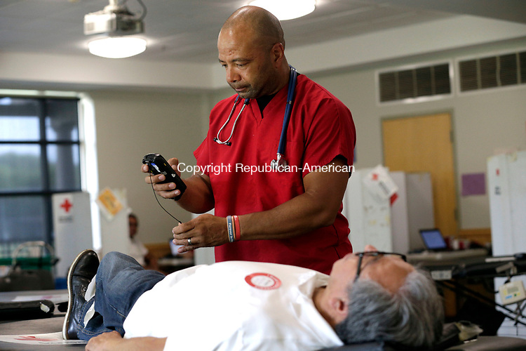 Waterbury, CT- 01 August 2017-080117CM01-  Phlebotomist Eric Carter, right,  prepares to take blood from Marco Martel of Waterbury, during the 5th annual David G. Devino Sr. blood drive at Chase Collegiate in Waterbury on Tuesday.    The annual event is held to honor Devino's memory by giving back to others, and raising awareness for autoimmune blood disorders and blood cancers.   Christopher Massa Republican-American