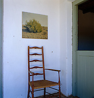 A high-backed wooden chair against the whitewashed wall in the hall