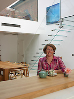Owner Jo Blythe sits at the breakfast bar in the kitchen dining area of her eco home