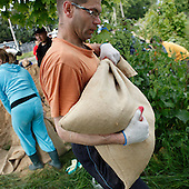 DOBRZYKOW, POLAND, MAY 24, 2010:.Villager carrying sand bag for the anti flood wall..The latest chapter of disastrous floods in Poland has been opened yesterday, May 23, 2010, after Vistula river broke its banks and flooded over 25 villages causing evacualtion of most inhabitants..Photo by Piotr Malecki / Napo Images..DOBRZYKOW, POLSKA, 24/05/2010:.Mieszkaniec niesie wortek z pieskiemi.  Najnowszy akt straszliwych tegorocznych powodzi zostal rozpoczety wczoraj gdy Wisla przerwala waly na wysokosci wsi Swiniary kolo Plocka..Fot: Piotr Malecki / Napo Images ..