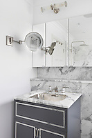 Grey and white marble has been used to clad the top of a metal basin and the walls of this bathroom