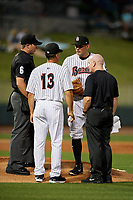 Birmingham Barons manager Omar Vizquel (13) and athletic trainer Cory Barton talk with starting pitcher Kyle Kubat (4) as umpire Matthew Brown looks on during a Southern League game against the Chattanooga Lookouts on May 1, 2019 at Regions Field in Birmingham, Alabama.  Chattanooga defeated Birmingham 5-0.  (Mike Janes/Four Seam Images)