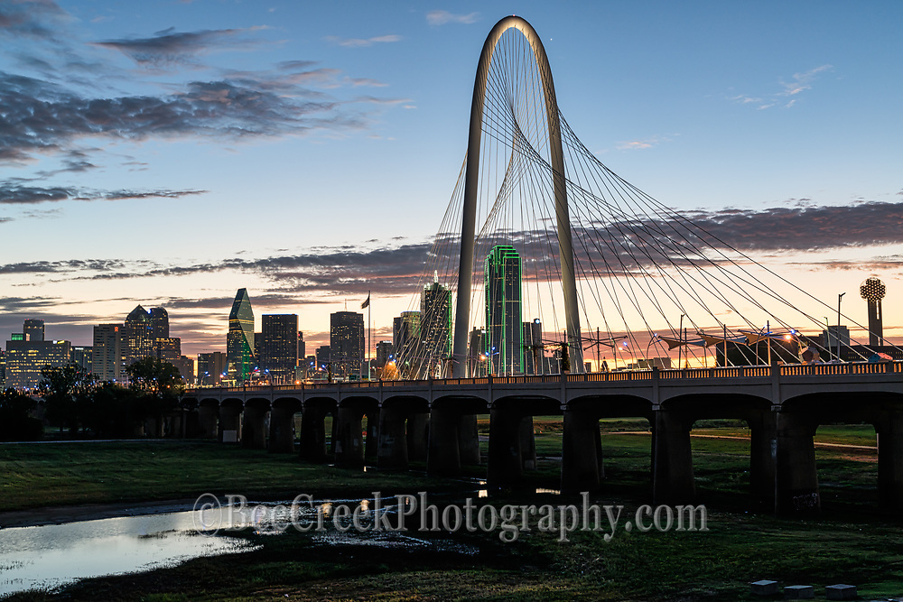Sunrise at Margaret Hunt Hill Bridge with Dallas skyline early morning glow before the sun comes up.  This image captured all the cityscape like the bank of America, Reunion Tower, and all the other skyscrapers along the Trinity River in downtown.  You can see the Continental Avenue Bridge or as it is called now the Ron Kirk Avenue Bridge which is a pedestrian bridge for viewing the killer sunset or sunrises over the city.