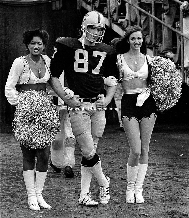 Raiders Dave Casper escorted by Raiderettes..to receive award before game..(1978 [photo/Ron Riesterer)