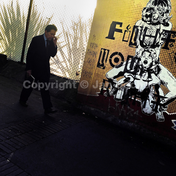"""A Colombian businessman walks in front of a stencil artwork, reading """"Fight for your right"""", in the center of Bogotá, Colombia, 17 February, 2016. A social environment full of violence and inequality (making the street art an authentic form of expression), with a surprisingly liberal approach to the street art from Bogotá authorities, have given a rise to one of the most exciting and unique urban art scenes in the world. While it's technically not illegal to scrawl on Bogotá's walls, artists may take their time and paint in broad daylight, covering the walls of Bogotá not only in territory tags and primitive scrawls but in large, elaborate artworks with strong artistic style and concept. Bogotá has become an open-air gallery of contemporary street art."""