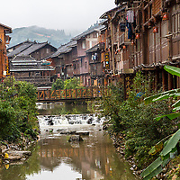Zhaoxing, Guizhou, China, a Dong Minority Village.  Shops and Houses Line Sides of Small River Running through the Village.