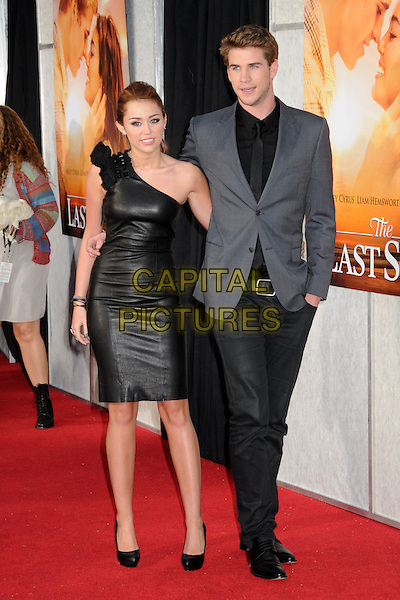 "MILEY CYRUS & LIAM HEMSWORTH .""The Last Song"" World Premiere held at Arclight Cinemas, Hollywood, California, USA, 25th March 2010..arrivals full length black one shoulder dress grey gray suit jacket shirt blazer arm around shoes heels walking leather shiny .CAP/ADM/BP.©Byron Purvis/AdMedia/Capital Pictures."