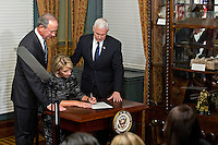 Betsy DeVos, United States Secretary of Education, center, signs an appointment affidavit next to U.S. Vice President Mike Pence, right, and her husband Dick DeVos Jr. in the Vice President's Ceremonial Office in Washington, D.C., U.S., on Tuesday, Feb. 7, 2017. DeVos squeaked through a history-making Senate confirmation vote to become U.S. education secretary, as Vice President Mike Pence broke a 50-50 tie and Republicans staved off last-minute defections that would have killed her nomination. Photo Credit: Andrew Harrer/CNP/AdMedia