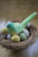 Detail of an Easter decoration of a green chick on a nest of small speckled Easter eggs