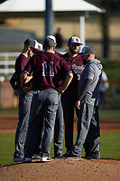 Concord Mountain Lions head coach Kevin Garrett (right) has a meeting on the mound during the game against the Wingate Bulldogs at Ron Christopher Stadium on February 2, 2020 in Wingate, North Carolina. The Mountain Lions defeated the Bulldogs 12-11. (Brian Westerholt/Four Seam Images)