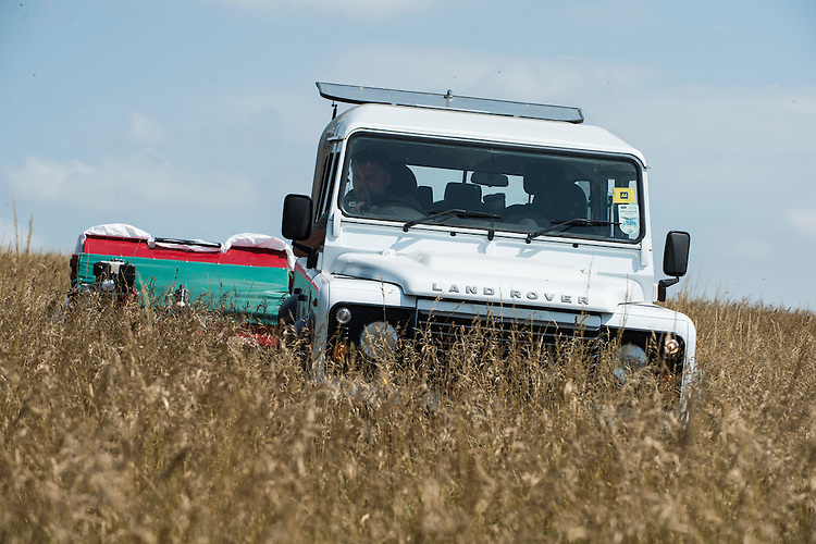 Members of Wakehurst Place  (Royal Botanic Gardens, Kew) collect seeds of meadow species with a brush harvester at Friston Gallops, Sussex. UK