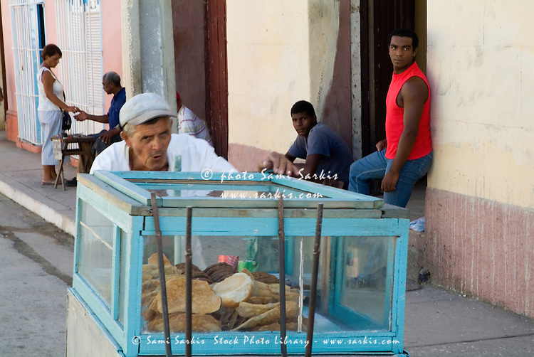 Man pushing a food cart along a street, Trinidad, Cuba.