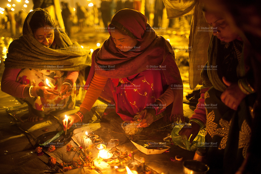 India. Uttar Pradesh state. Allahabad. Maha Kumbh Mela. A group of thrre women, all Indian Hindu devotees, celebrate at night a puja on the banks in Sangam. Puja (reverence, honour, adoration, or worship) is a religious ritual performed by Hindus as an offering to various deities. The Kumbh Mela, believed to be the largest religious gathering is held every 12 years on the banks of the 'Sangam'- the confluence of the holy rivers Ganga, Yamuna and the mythical Saraswati. The belief is that bathing and taking a holy dip will wash and free one from all the past sins, get salvation and paves the way for Moksha (meaning liberation from the cycle of Life, Death and Rebirth). Bathing in the holy waters of Ganga is believed to be most auspicious at the time of Kumbh Mela, because the water is charged with positive healing effects and enhanced with electromagnetic radiations of the Sun, Moon and Jupiter. The Maha (great) Kumbh Mela, which comes after 12 Purna Kumbh Mela, or 144 years, is always held at Allahabad. Uttar Pradesh (abbreviated U.P.) is a state located in northern India. 12.02.13 © 2013 Didier Ruef