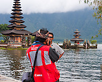 "One of the many local vendors takes a souvenir snapshot of a tourist by the lake, at the iconic spot in the grounds of the Hindu temple of Ulun Danu at Candikuning, on Bali, Indonesia.  Located in the high hills of the Bedugul, about 30 miles north of Bali's capital city of Denpasar, the temple is built on the shores of the crater Lake Bratan (formed from the sunken crater of a long-dormant volcano).  Much of the inner precincts of the temple is closed to the (non-Hindu) public, but the gardens are spectacular and feature fabulous shrines, statuary, and views.  The iconic tourist image is the two ""water shrines,"" which these days are usually partially submerged in the waters of Lake Bratan."