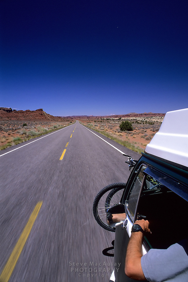 V.W. Westfalia Camper cruising down the desert highway, Utah 95, Near Natural Bridges National Monument..Shot by hanging a camera on an articulated camera support attached to the roof rack and firing the shutter remotely.