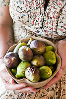 A woman holds a bowl of freshly picked figs