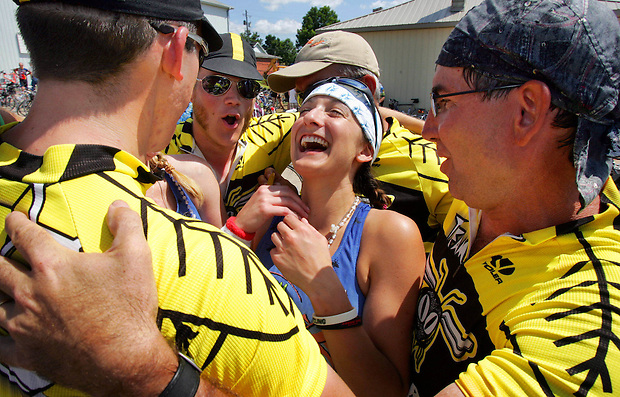 "RAGBRAI rider Lindsey Olson of Chicago is surrounded and ""stung"" by Team Killer Bees members, from left, David Failing of Ames, Scott Taylor of Ames, Terry Kremer (obstructed) of LaMott, and Ted Huseman of Chicago while reveling Wednesday in Lacona on RAGBRAI XXXVII.  The team traditionally surrounds fellow riders, chants and places stickers on their bodies.  Many riders lingered in Lacona to socialize and unwind on one of the shorter distance rides of the week."