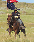 A calvary soldier on horseback charges forward and is carrying the troop flag in battle during the 13th annual Custer Battle of the Little Bighorn reenactment in Hardin Montana. 8x10 format. Model release.