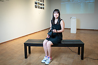 "Lynn He '19, chemistry major, worked on ""Hawai'i Through the Lens"" a photographic exhibition by the students in ARTH390 from their class trip to Hawai'i. Photographed on April 25, 2019 in Weingart Gallery.<br /> (Photo by Marc Campos, Occidental College Photographer)"