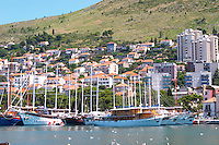 Several beautiful wooden cruising, sailing and fishing boats ships yachts painted white moored along they key in the harbour. Modern buildings creeping up the hillside. Luka Gruz harbour. Dubrovnik, new city. Dalmatian Coast, Croatia, Europe.
