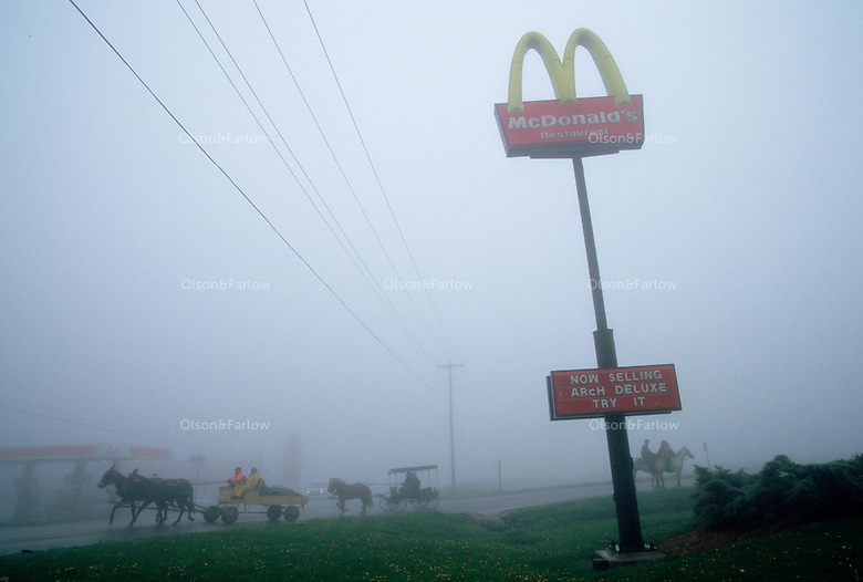 Wagons and horses roll out of McDonalds in a thick fog as the <br /> wagon train heads west. An annual reenactment brought westward bound caravans to the Pike festival, although the first settlers did not stop for fast food coffee along their route on Keyers Ridge, Maryland.