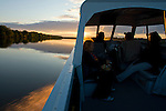 Residents of Fort Chipewyan sail down the Athabaska River. Many residents of Fort Chipewyan have cabins on the land. They try to maintain some of their attachment to Mother Earth, which is exceedingly difficult with the dangers of eating the fish and disappearance of wildlife due to industrial development upstream.